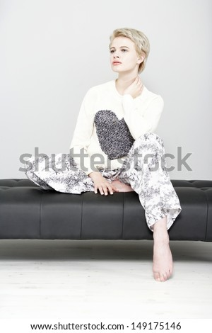 Beautiful young woman relaxing on her sofa at home in pyjamas