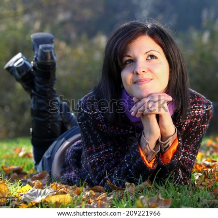 Beautiful young woman relaxing on the ground in autumn - stock photo