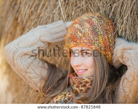 Beautiful young woman relaxing under a hay stack in autumn.