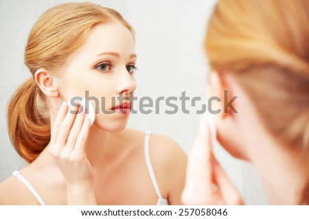 beautiful young woman removes makeup with face skin cotton pad - stock photo