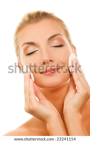 Beautiful young woman removing cosmetics with cleansing pad