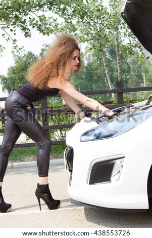 beautiful young woman repairing the car on the road