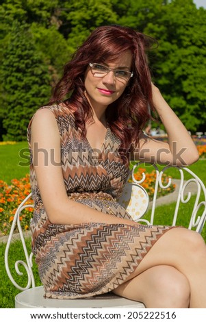 Beautiful young woman resting on a chair outdoors in a park