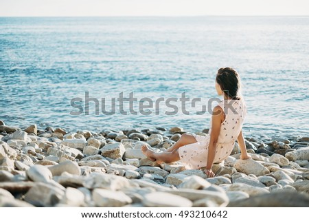 Beautiful young woman resting on pebble coast and enjoying view of sea