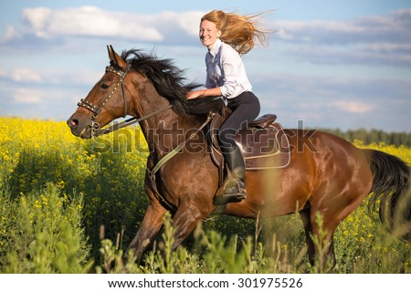 Beautiful young woman riding a horse.