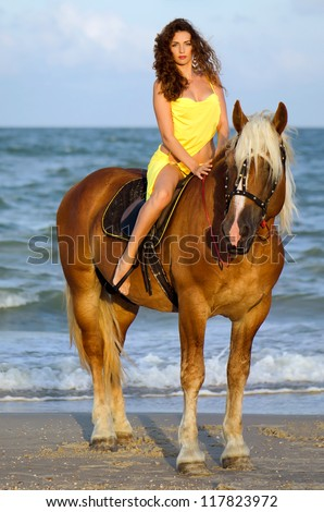 Beautiful young woman riding a horse on the beach - stock photo
