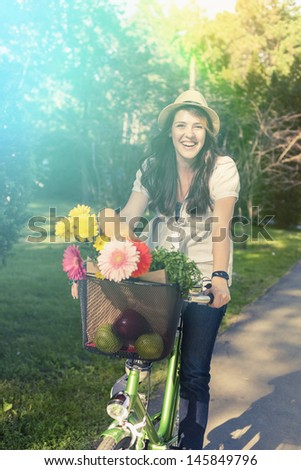 Beautiful young woman riding bicycle with hat on her head enjoying summer time.  - stock photo
