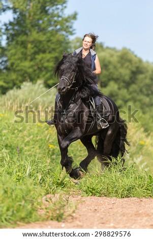 Beautiful young woman riding black stallion. - stock photo