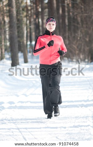 Beautiful young woman running at winter forest - stock photo