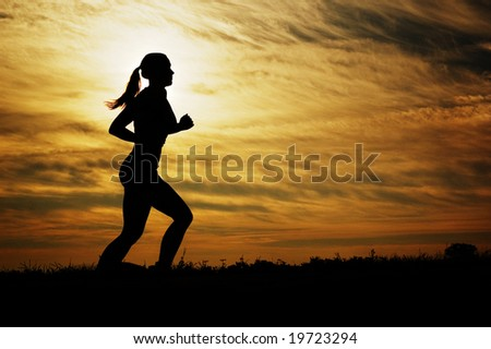 Beautiful young woman running in front of a sunset. - stock photo