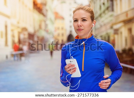 Beautiful young woman running in the city competition and listening to the music - stock photo