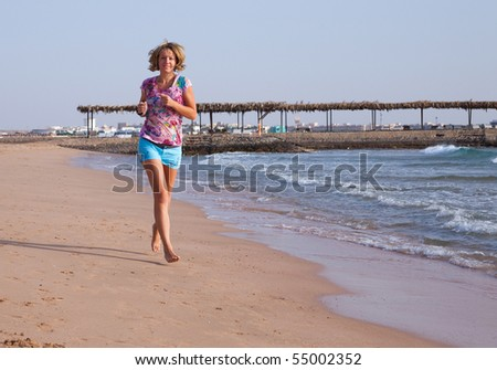 Beautiful young woman running on a beach - stock photo