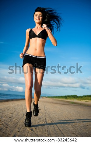 Beautiful young woman running on the beach - stock photo