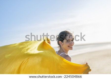 beautiful young woman running on the beach leaving steal his yellow scarf into the sunset - stock photo