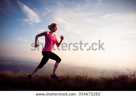 beautiful young woman runs on a mountain path at sunrise - stock photo