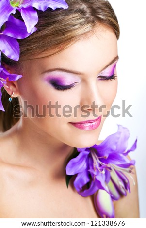 beautiful young woman's face with purple flowers and makeup - stock photo