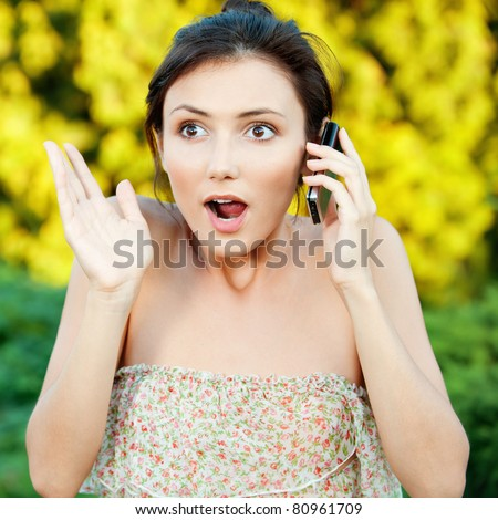 Beautiful young woman said by cell phone on natural background - stock photo