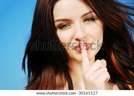Beautiful young woman saying shh with her finger to her lips outdoors - stock photo