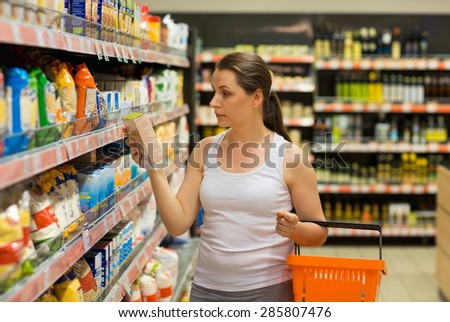 Beautiful young woman shopping for cereal, bulk in a grocery supermarket - stock photo