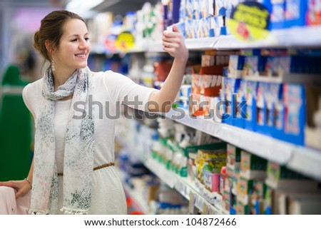 Beautiful young woman shopping for diary products at a grocery store/supermarket (color toned image) - stock photo