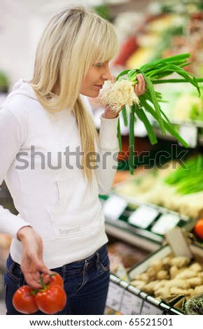 Beautiful young woman shopping for fruits and vegetables in produce department of a grocery store/supermarket (shallow DOF; color toned image) - stock photo