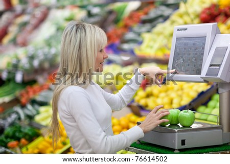 Beautiful young woman shopping for fruits and vegetables in produce department of a grocery store/supermarket (shallow DOF) - stock photo