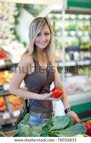 Beautiful young woman shopping for fruits and vegetables in produce department of a grocery store/supermarket - stock photo