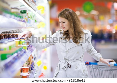 Beautiful young woman shopping for fruits and vegetables in produce department of a grocery store/supermarket (color toned image) - stock photo