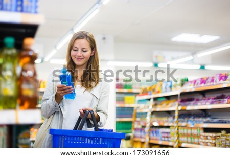 Beautiful young woman shopping in a grocery store/supermarket (color toned image) - stock photo