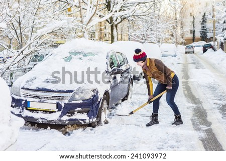 Beautiful young woman shoveling her car after a Snowstorm  - stock photo