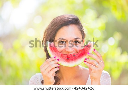 Beautiful young woman showing a slice of watermelon as a smile. She is caucasian, she wear a white dress and she has a braid on the shoulder. Summer and lifestyle concepts. - stock photo