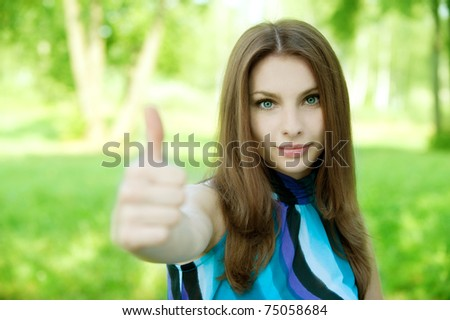 beautiful young woman showing a thumb on a green background