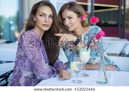 Beautiful young woman showing something her friend - stock photo