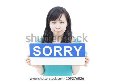 beautiful young woman showing SORRY sign, isolated on white background - stock photo