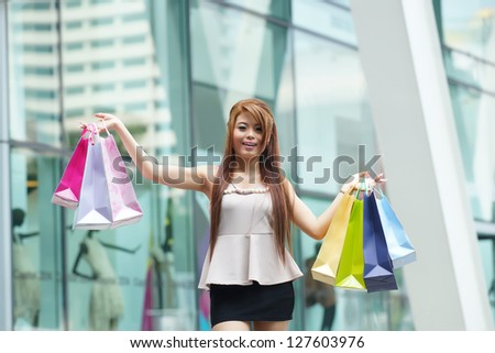 Beautiful young woman shows an ecstatic expression while holding shopping bags outside shopping mall.