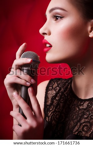 Beautiful young woman singer with microphone