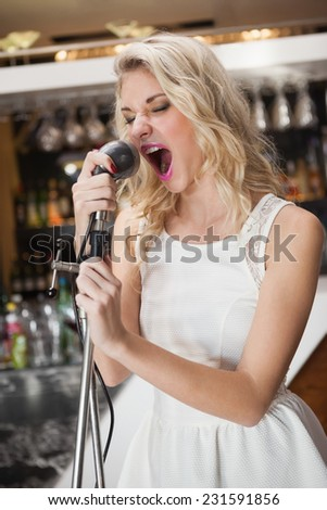 Beautiful young woman singing into a microphone at the nightclub - stock photo