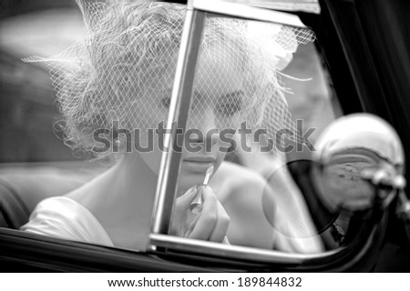 Beautiful young woman siting in the car. Retro style. - stock photo