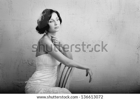 Beautiful young woman sits on a chair. Retro Style - stock photo