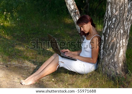 Beautiful young woman sits on a grass in a park with the laptop.