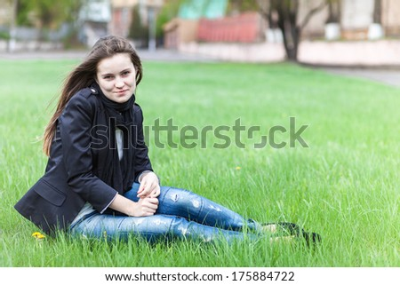 Beautiful young woman sits on a green lawn in the city