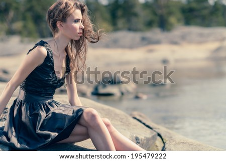 Beautiful young woman sits on the rock, sunny day on beach