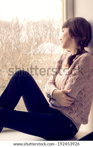 Beautiful young woman sitting at the window.  Dreaming young girl - stock photo