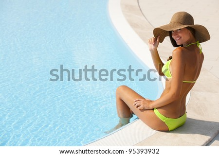 Beautiful young woman sitting by swimming-pool - stock photo