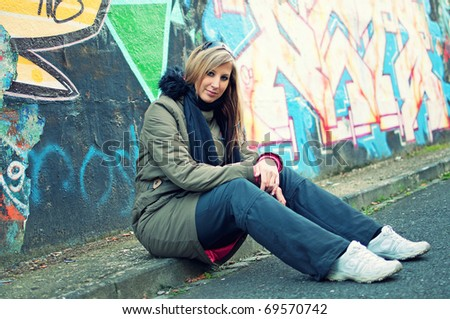 Beautiful young woman sitting by the road in front of graffiti wall - stock photo