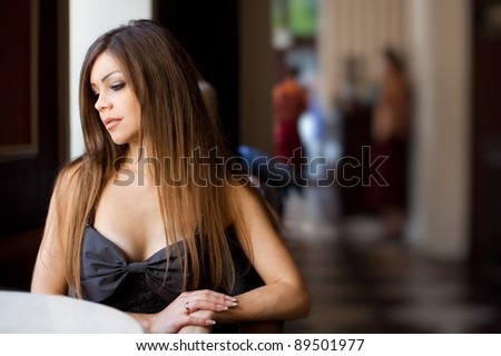 Beautiful young woman sitting in a cafe alone - stock photo