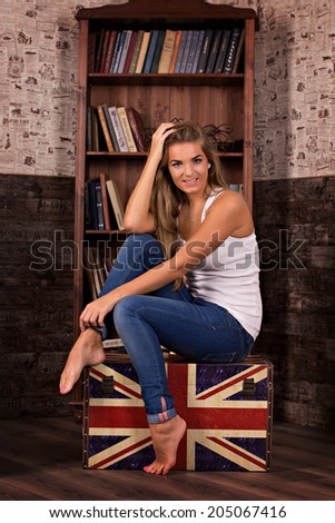 beautiful young woman sitting in a chair near a bookcase - stock photo
