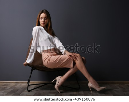 Beautiful young woman sitting in a chair on grey wall background