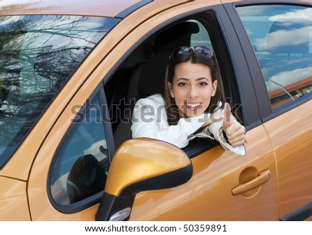 Beautiful young woman sitting in a new car with thumb up - stock photo