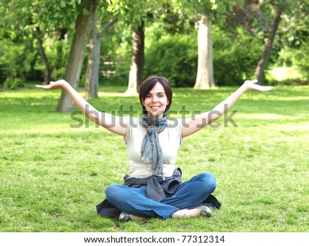 Beautiful young woman sitting in a park - stock photo